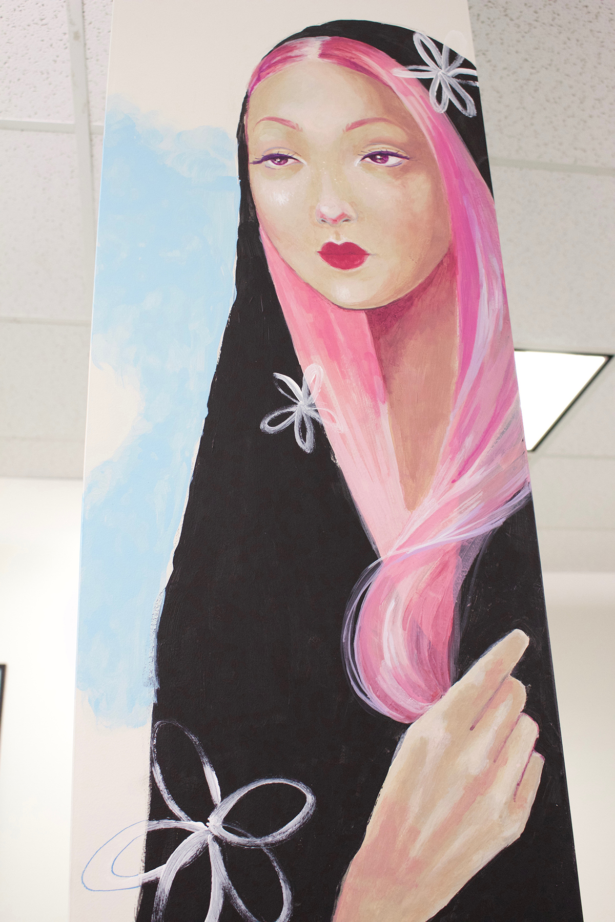 Shailin Messer painting of a woman with pink hair with a black blanket on her head on one of the columns at CommCreative